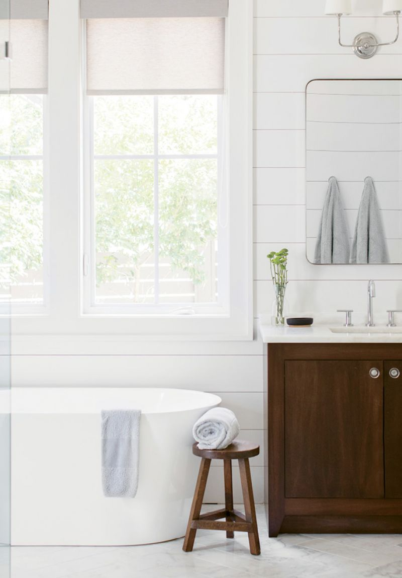 R&R: In the master bath, a large soaking tub overlooking the backyard separates his-and-her marble-topped vanities. An expansive shower with frameless glass and penny marble tile completes the retreat.