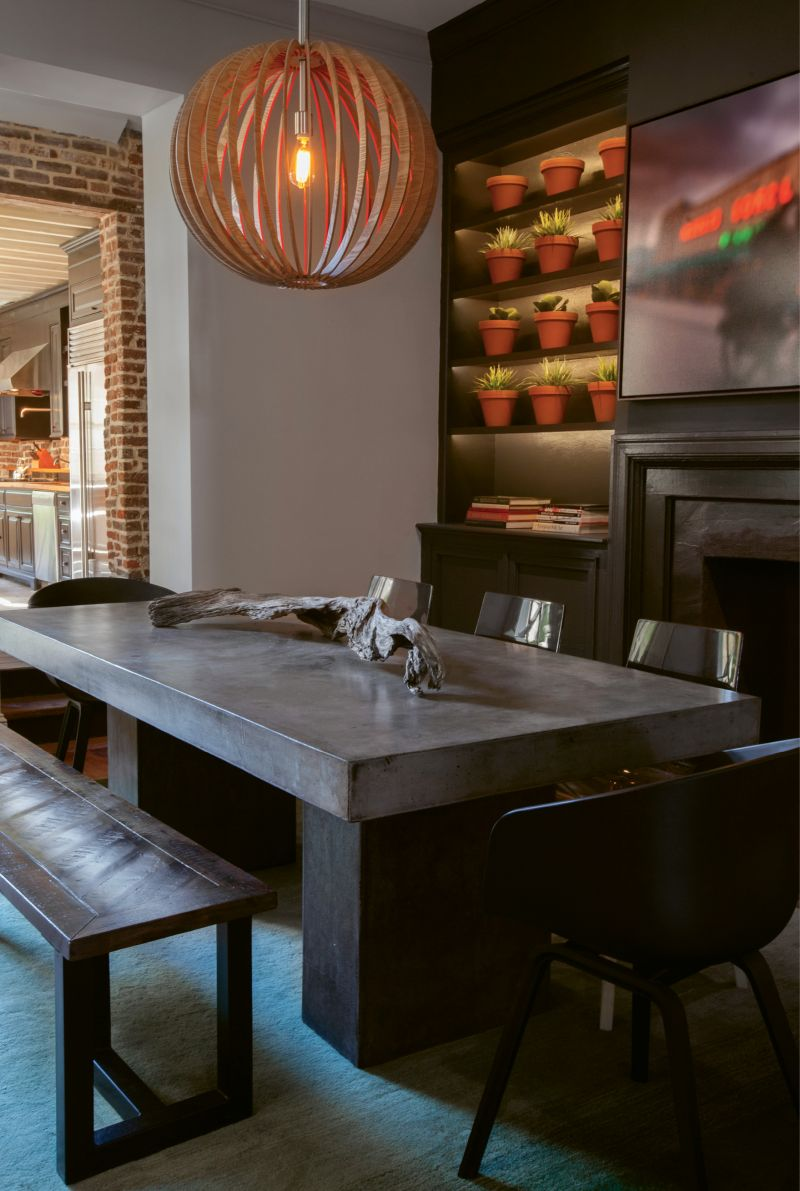 Paint It Black: In the dining room, Naylor had the idea to transform the fireplace surround and adjacent built-ins with a few coats of black paint. A wall of succulents in terra-cotta pots and a John Duckworth photograph of the old Morris Sokol building pop against the moody backdrop.
