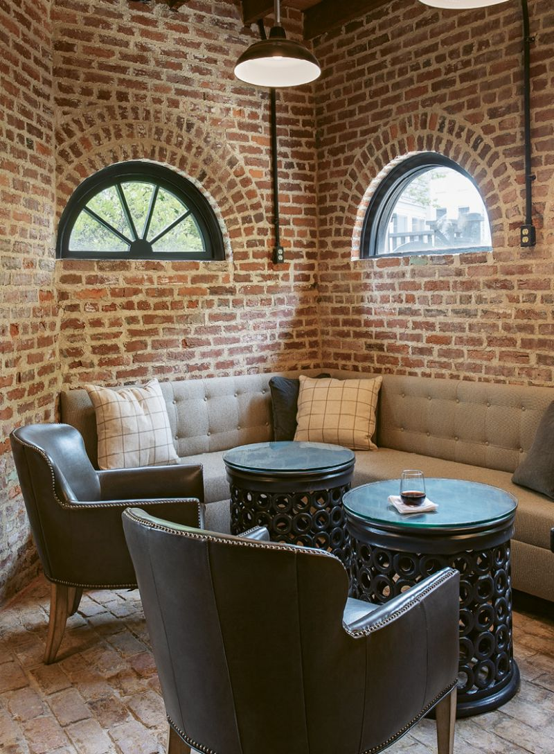 """For this lounge area, designer Kristin Peake echoed the motif with cylindrical side tables, spinning barstools, and round mirrors to soften the hard lines of the floorplan and exposed brickwork. See the electrical outlets mounted on the walls? That's another flood-proofing trick to prevent inevitable storm surges from wiping out wiring that runs along ground level. There's no insulation on the bottom three feet of this floor. """"It's all brick, which can take the water,"""" says Rick. """"We'll just pump anything out."""""""