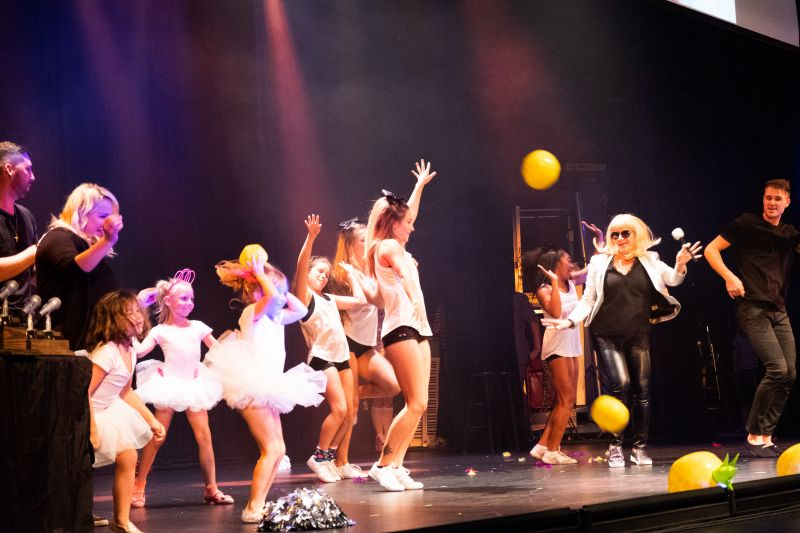 Buffie Bell Lilly is joined on stage by friends, cheerleaders from Flip Gym Cheer, and a group of tiny ballerinas, including her daughter.
