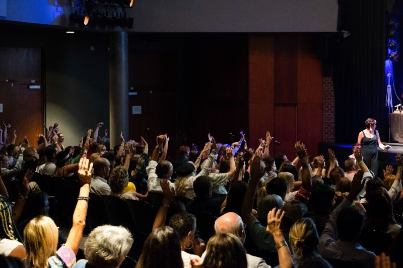 In a powerful moment, the majority of audience members raise their hands, affirming that nearly everyone has been affected by lung disease.