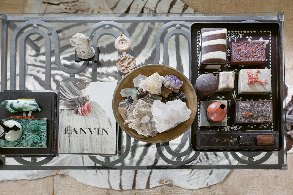 Collections of crystals and antique boxes are displayed on the coffee table