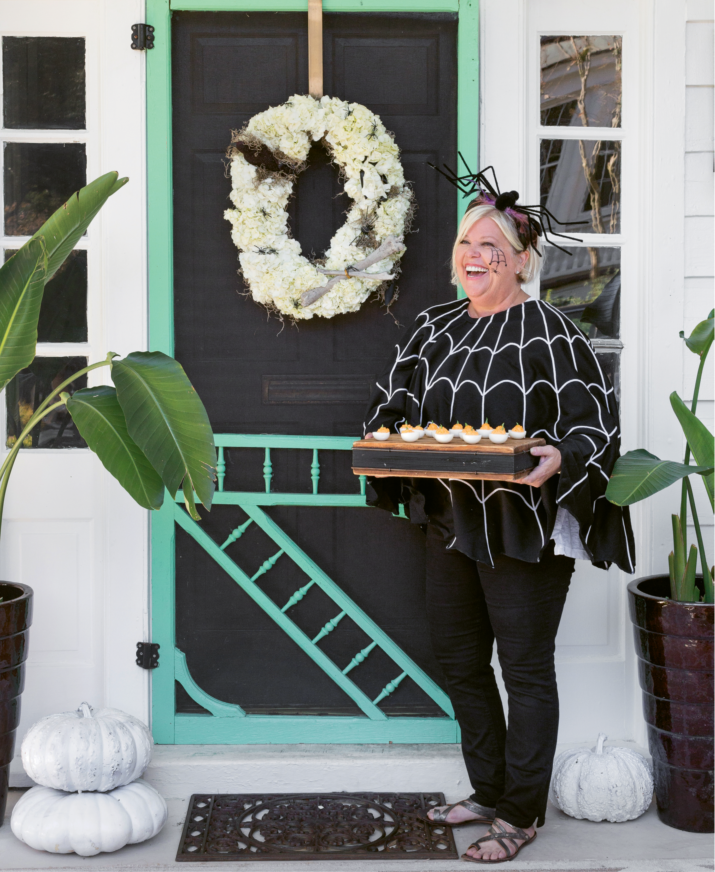 """For 15 years now, event designer Lisa Thomas's lair has been the """"it"""" place for trick-or-treaters—and their chaperones. As for adding a little freaky flair to your own front door, she says all that's needed is a classic wreath (like this hydrangea number by Lisa's floral business, Out of the Garden), florist wire, fluffy grasses, and creepy-cool add-ons—think faux crows and leggy spiders."""