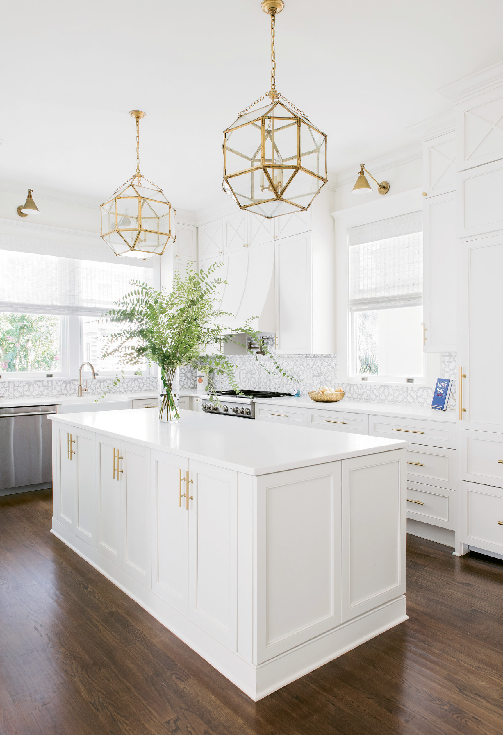 "LIGHT & BRIGHT: ""The kitchen is a good example of what Melissa did so well, filling every nook and cranny and making them useful in some way,"" says Alison. Fireclay backsplash and gold pendants and sconces add glamour to the utilitarian space."