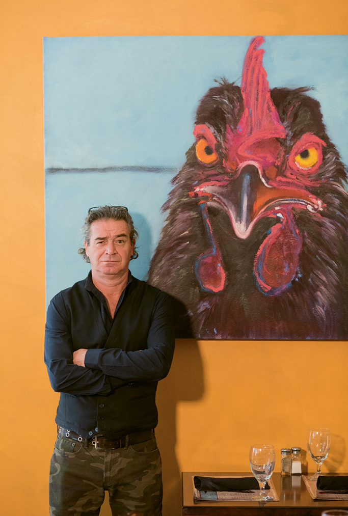 Chick Magnet: Goulette chef-owner Perig Goulet poses with one of the cafe's cheeky chicken paintings, this one by local artist Sybil Fix.
