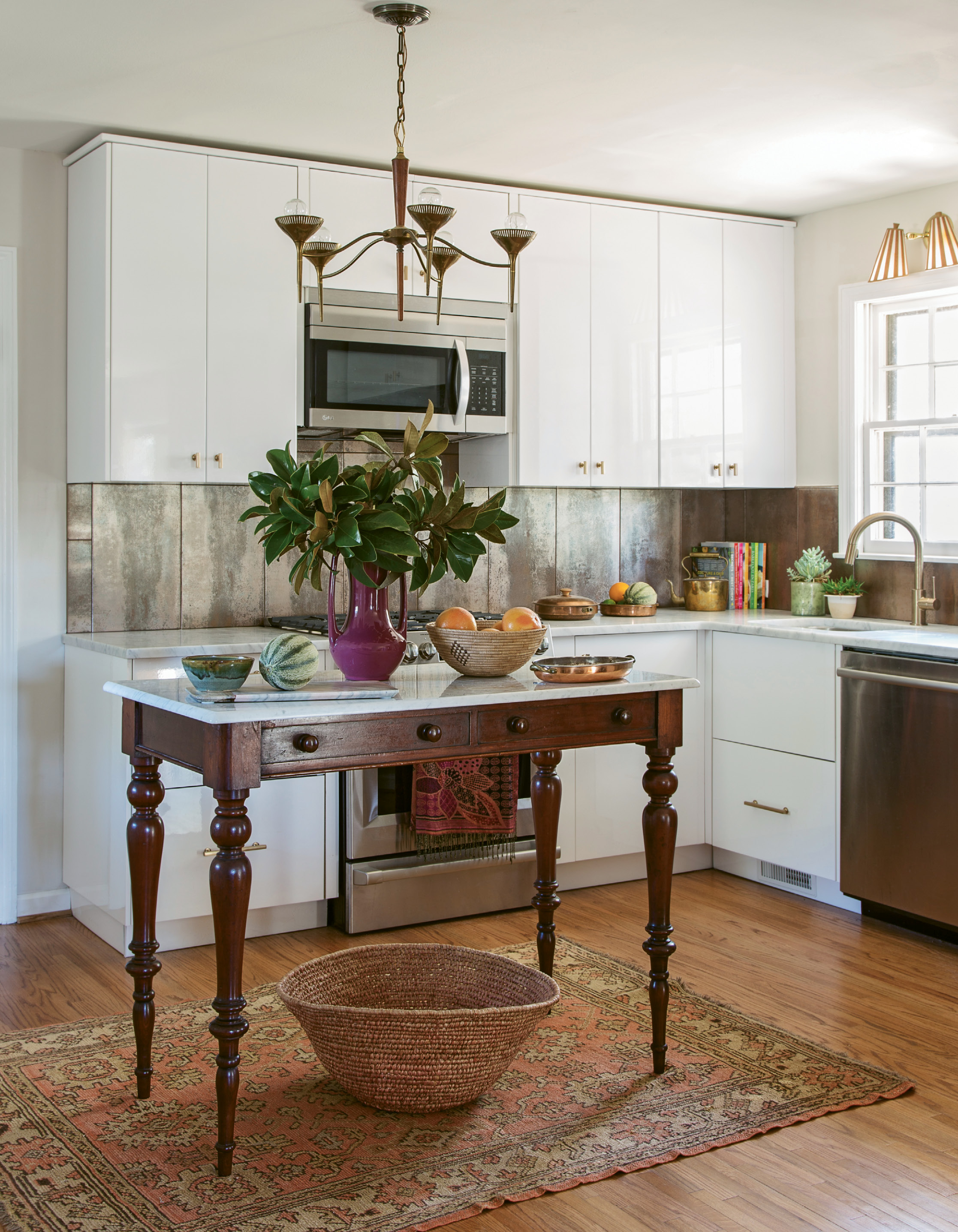 FRESH TAKE: High-gloss cabinets and a cool coppery backsplash help modernize the retro kitchen. But antique pieces—such as a brass-and-wood mid-century light fixture and a marble-top table reimagined as an island—lend vintage charm that's cohesive with the rest of the abode.