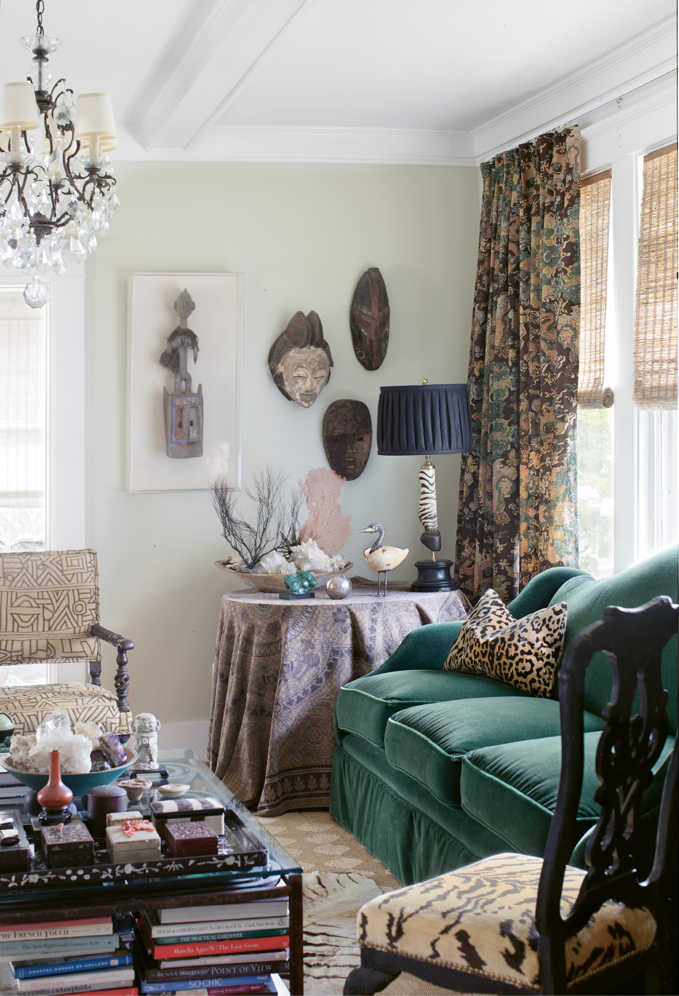 """Traditional furnishings, such as 18th-century Swedish rococo chairs upholstered in Scalamandre's """"Le Tigre"""" silk velvet and a 19th-century Jacobean armchair with antique African Kuba cloth, mingle with African masks and floral-style arrangements of sea coral."""