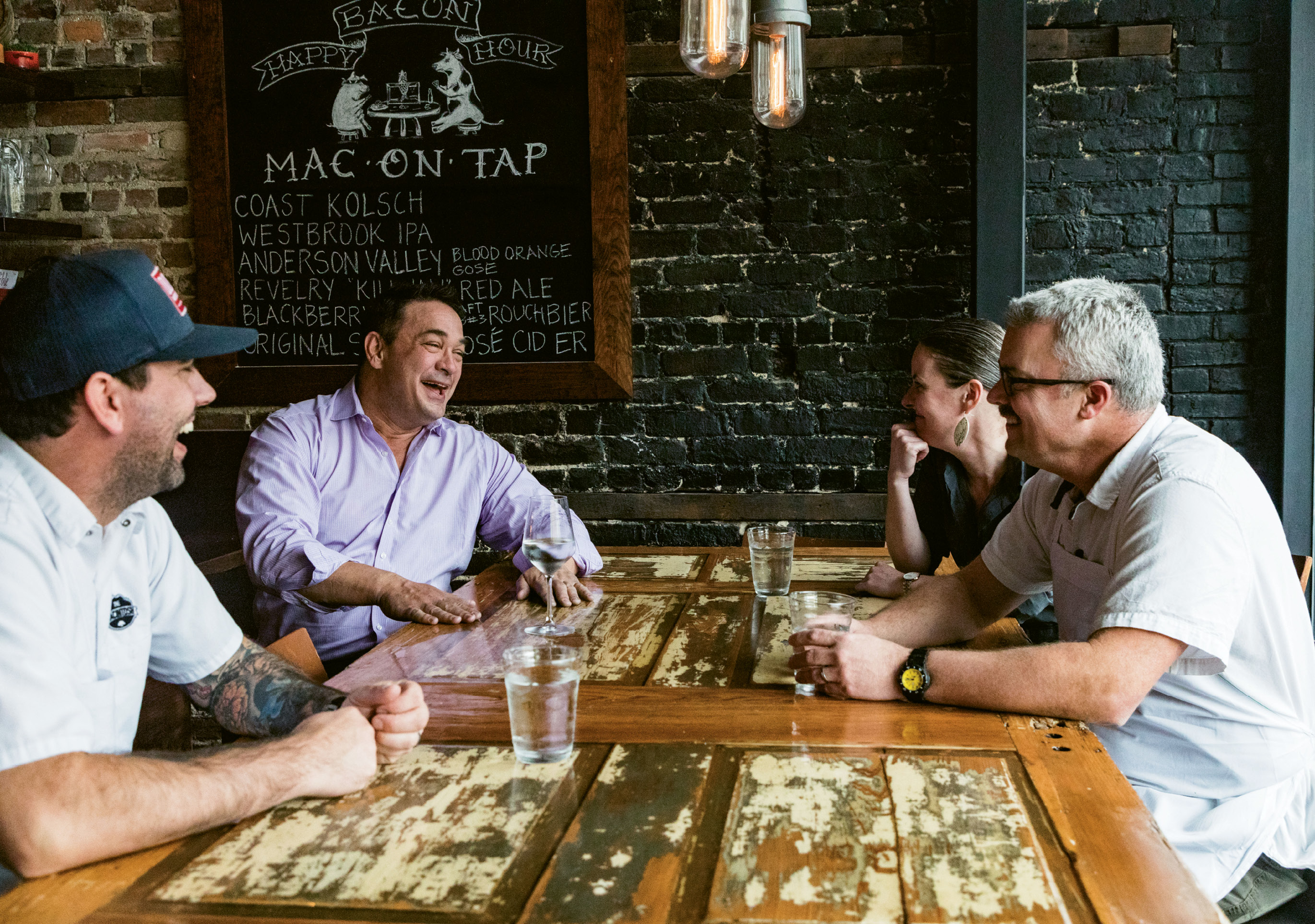 """Palmer catches up with his team at The Macintosh, including (left to right) executive chef Jacob Huder, general manager Julie Hennigan, and chef-partner Jeremiah Bacon. As a sober person working in the restaurant business, Palmer loves what he does, and it shows. As far as his beverages of choice, he says, """"Sparkling water, of course, but I love the new trend of nonalcoholic cocktails. I'm so glad the industry is finally recognizing that sober people like to drink fun things too. And, by the way, we are happy to pay for them!"""""""
