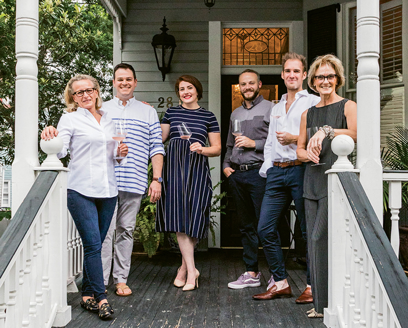 Before dinner, Trudi Wagner (far left) and Patty Floersheimer (far right) greet guests with glasses of rosé on the porch of their downtown home.