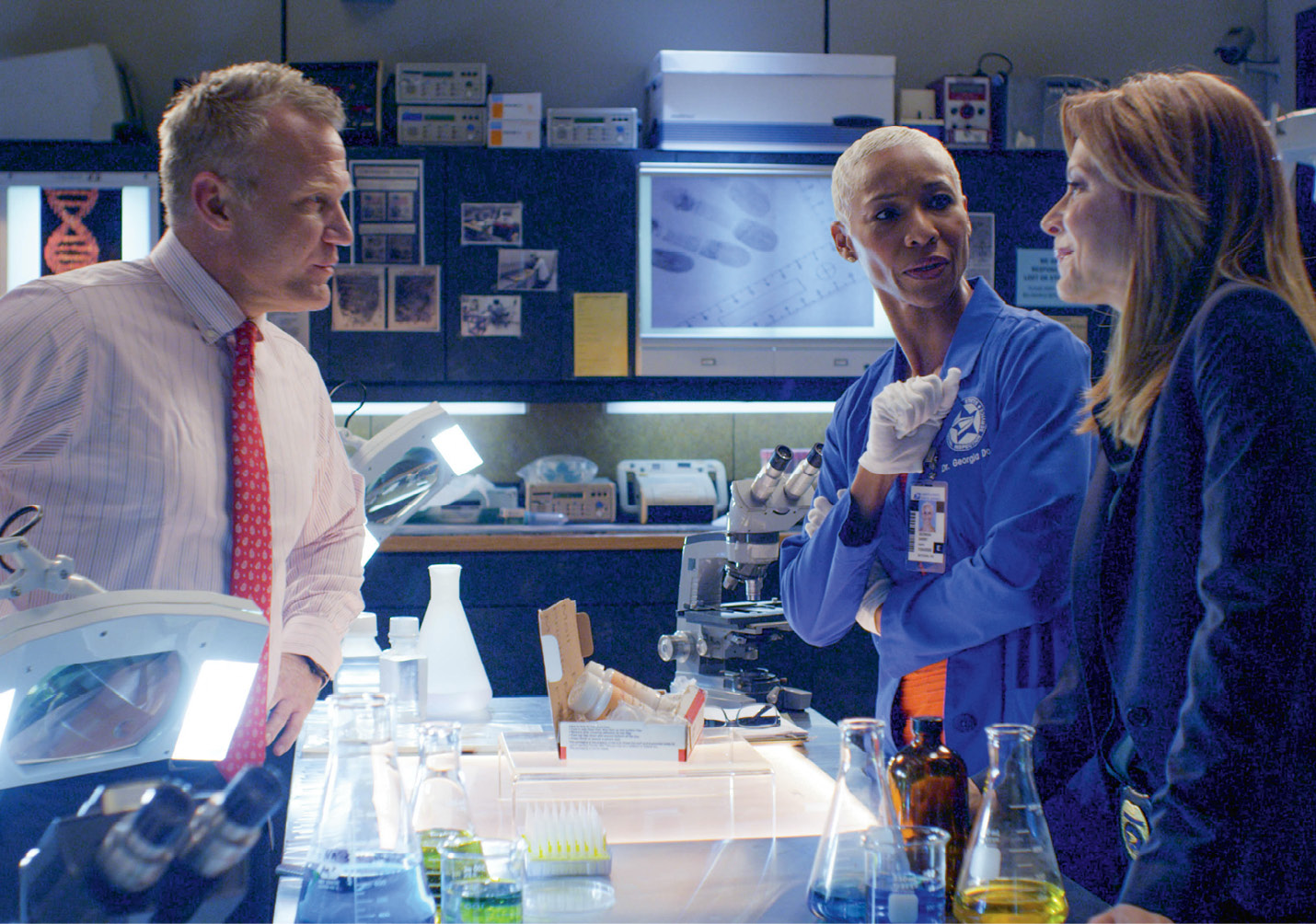 """The Inspectors' cast includes (above, left to right) Terry Serpico, Charmin Lee, and Jessica Lundy, shown in the """"crime lab."""""""