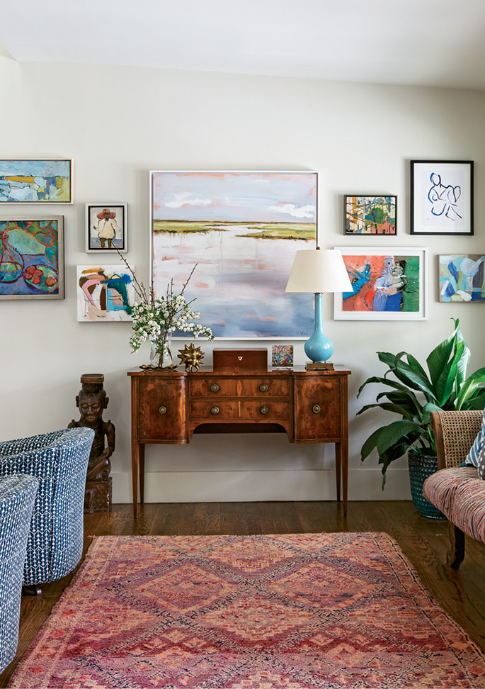 """Changing Scenery: This gallery wall in the living room is always in flux. """"I constantly change it out,"""" Allison says. Works by Charleston Artist Collective members dominate this iteration, including pieces by Shannon Wood (center) and Lynne Hamontree (top right)."""