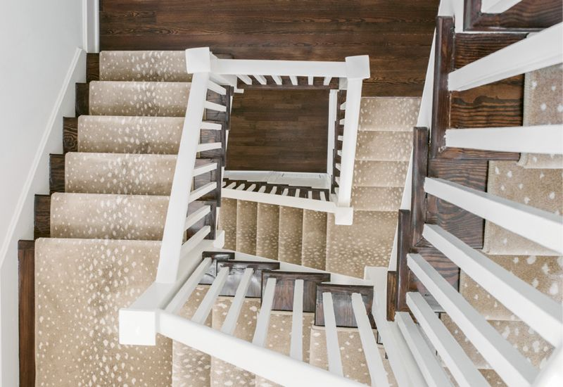 SURE-FOOTED: The team took great care to restore the existing handrail and spindles of the winding staircase. Thanks to a neutral-hued animal-print runner, socked feet and pups' paws are padded from floor to floor.
