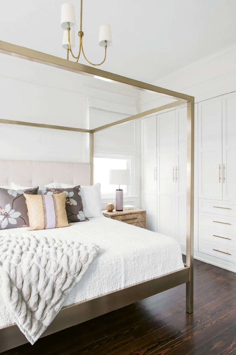 In the bedroom, sleek furnishings (like the bed and side tables from One Kings Lane, pillows and lamps from Fritz Porter, and brass chandelier by Visual Comfort from Circa) are clean-lined and serene. In lieu of a walk-in closet—which was sacrificed for a larger playroom—wall-to-wall built-ins provide plenty of storage.
