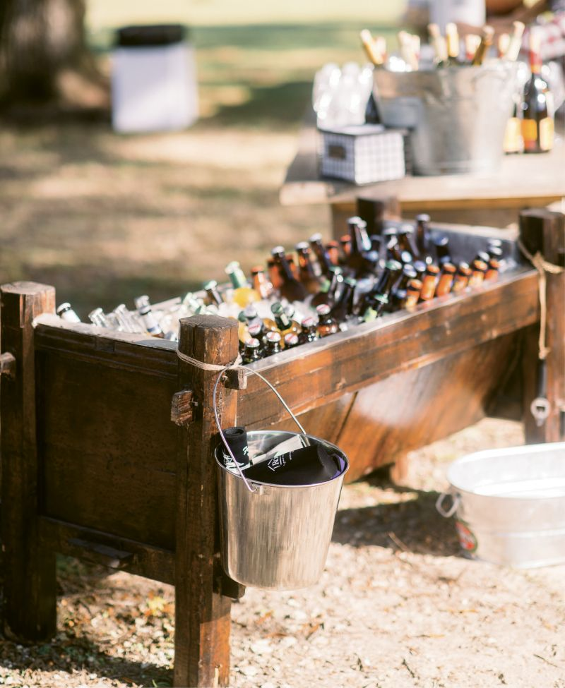 Bottoms Up: A wooden trough rented from Snyder Events kept the serve-yourself beer stash iced while a galvanized pail secured with rope held koozies and added to the day's rustic aesthetic.