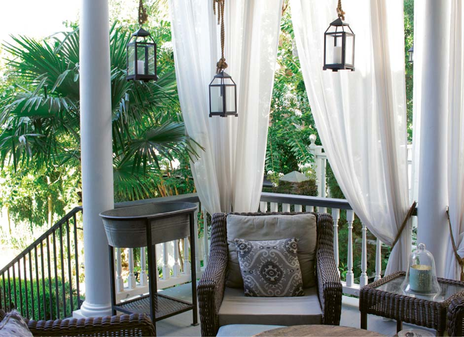 "Scenic Overlook: Shaded by palm trees and sheer white curtains, the back porch is outfitted for year-round living with a whirring ceiling fan, a quartet of comfy wicker chairs, and a galvanized tub for icing drinks. ""We're out here constantly,"" says Susan."